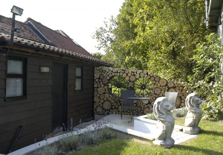 Patio with stone lions and wall made from logs and wheels